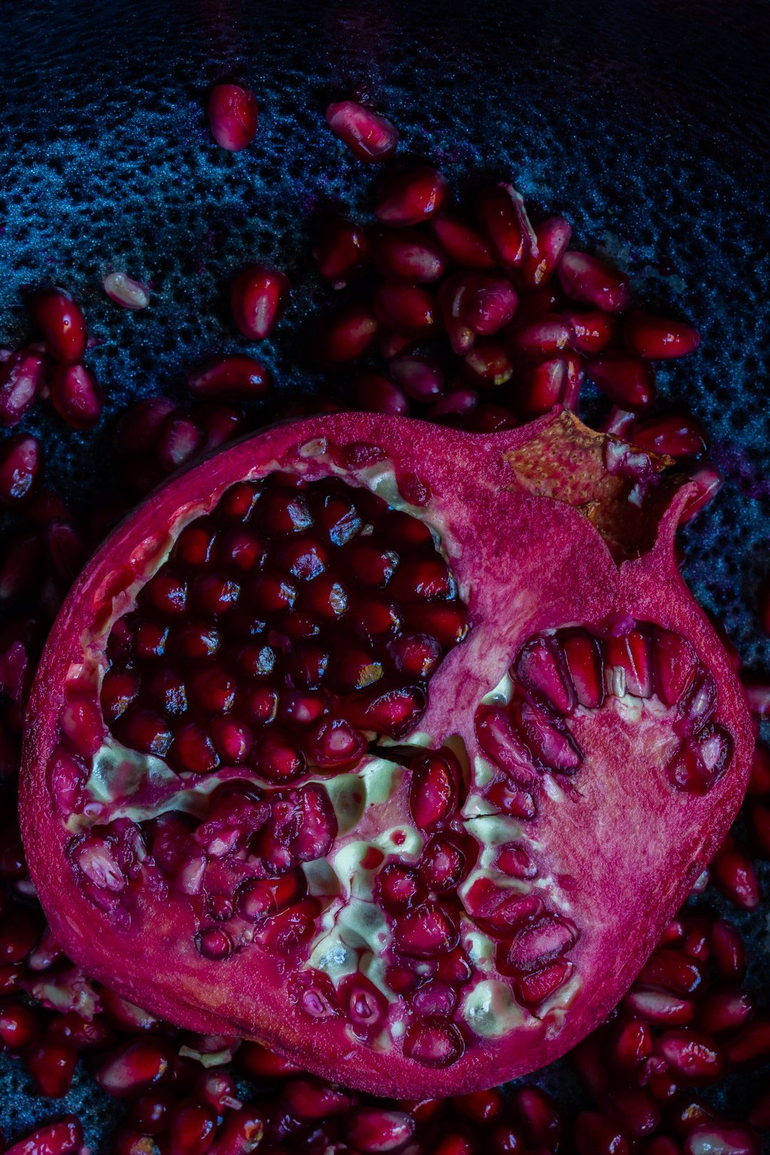 pomegranate split open on black textured background from above used to make grenadine