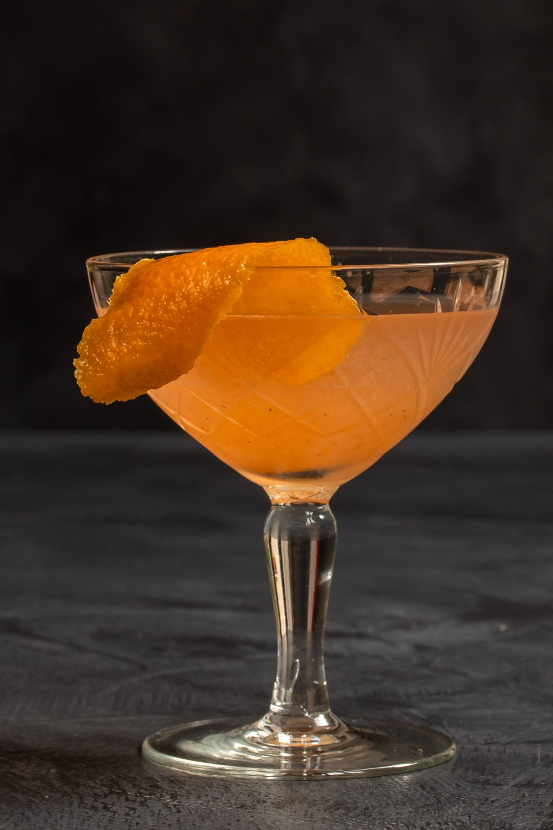 quince apple jam gin sour cocktail solo on grey textured background