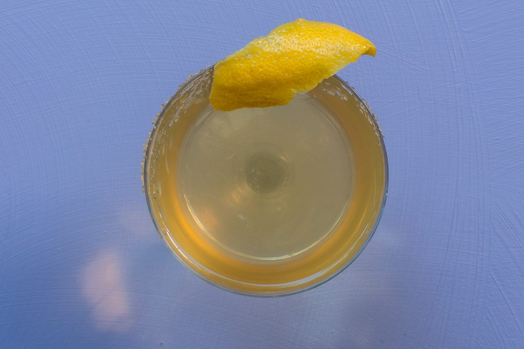 Fancy quince brandy champagne cocktail from above on light purple background