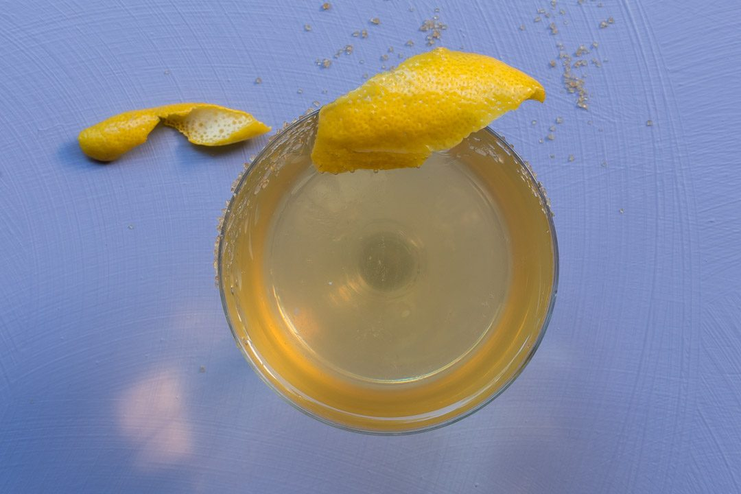 Fancy quince brandy champagne cocktail from above with lemon twist on light purple background