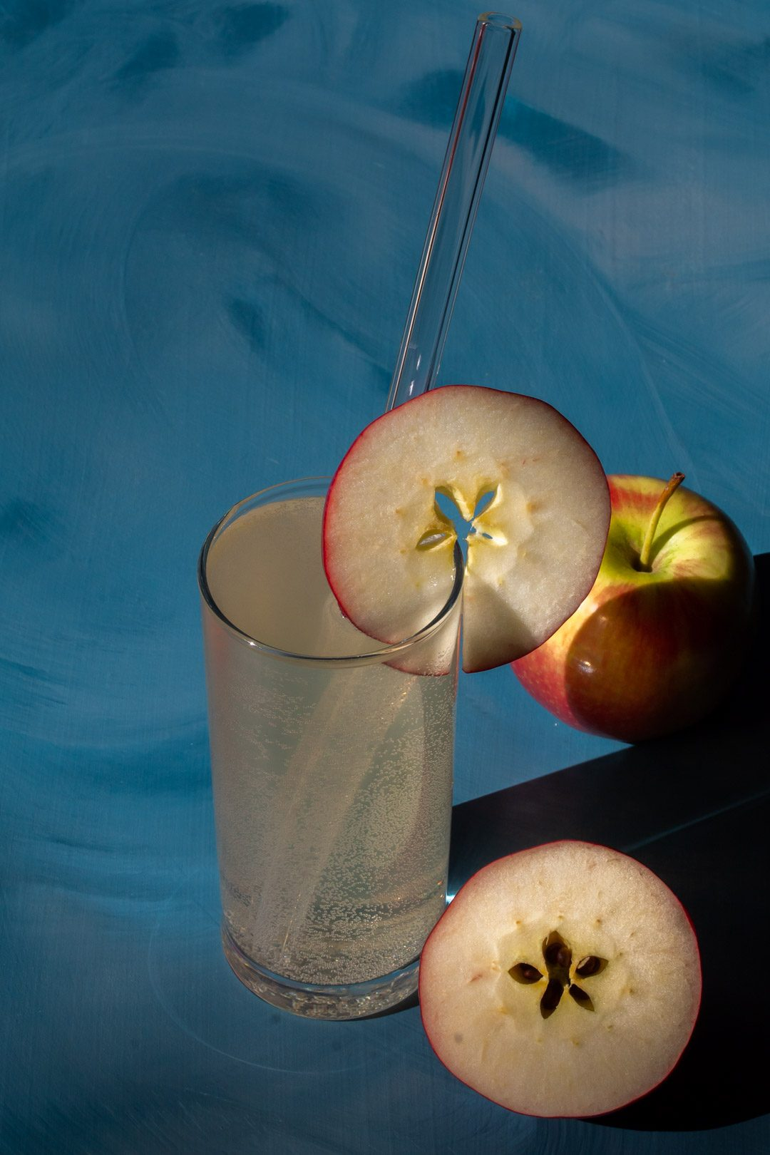 apple shrub gin fizz cocktail from 45 degrees on blue background with apples