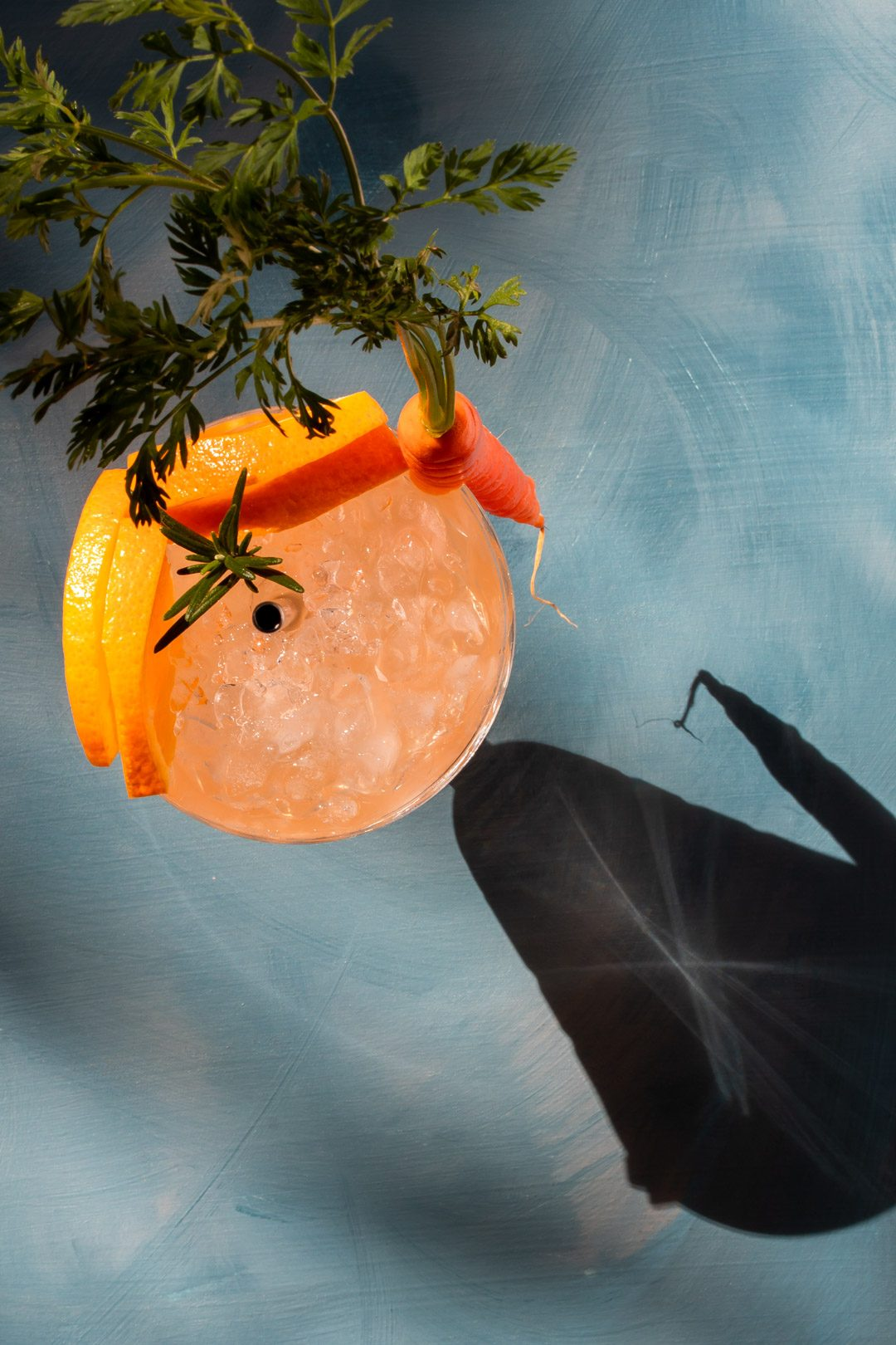 Carrot shrub daisy cocktail from above on blue background with shadows and hard light