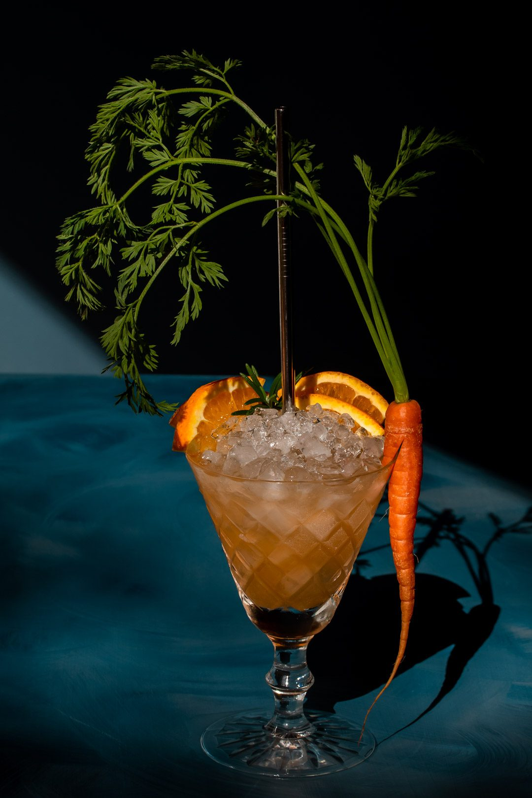 carrot shrub daisy cocktail from 45 degrees with hard light and shadows