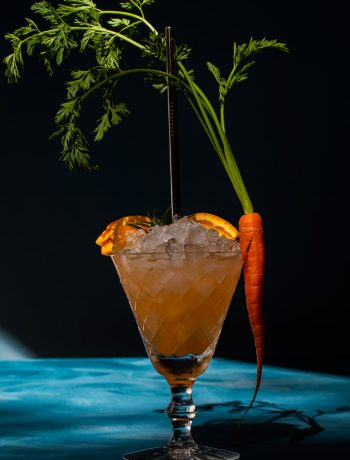 carrot shrub daisy cocktail with deep shadows on blue background