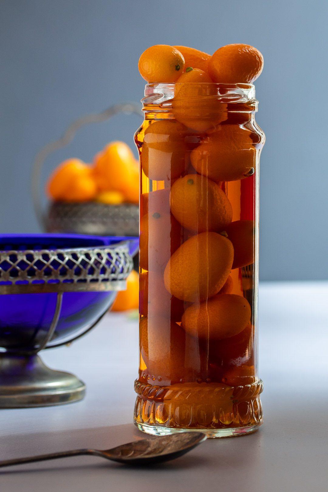 cumquat brandy with blue glass jug and dish of cumquats in background