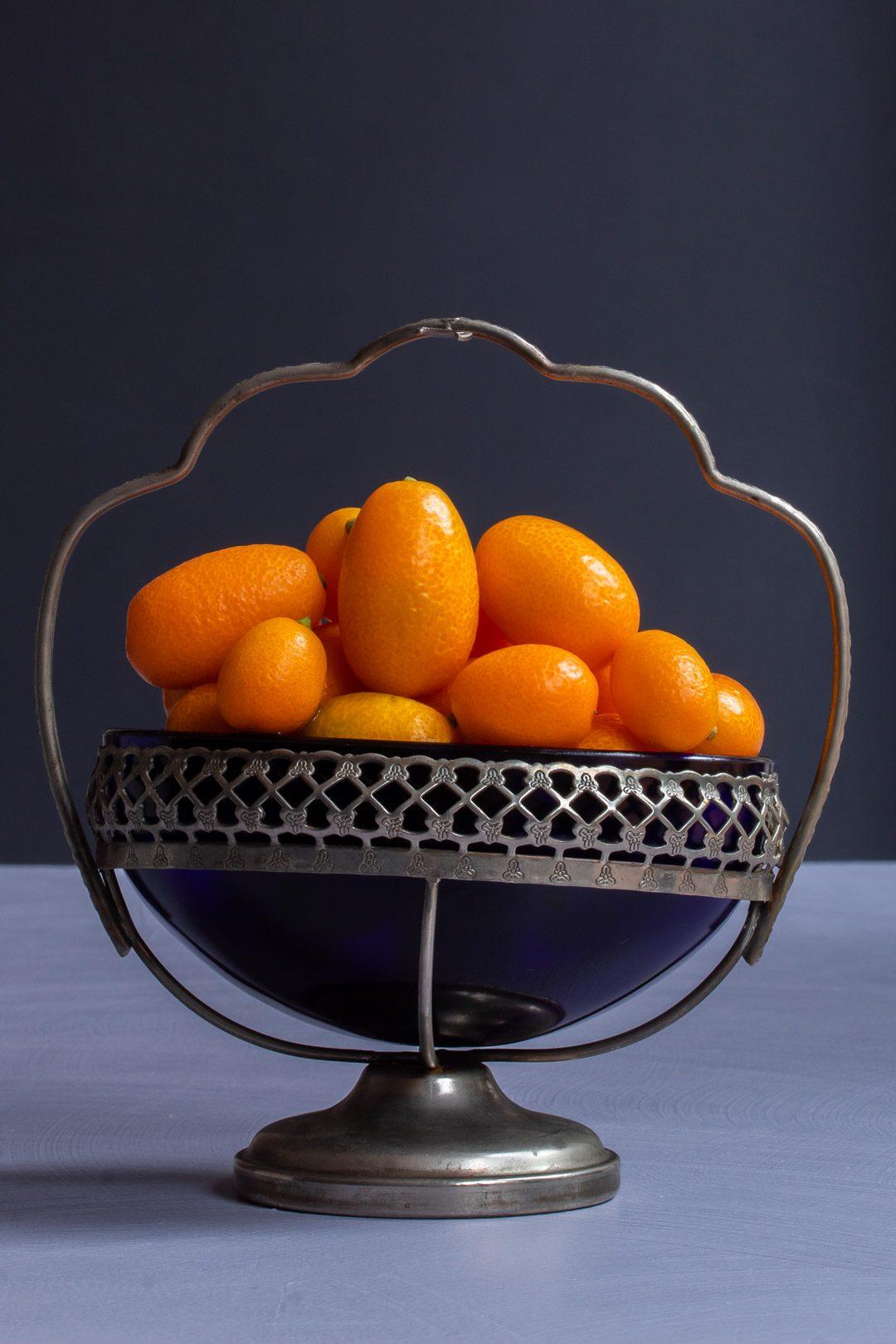 making cumquat brandy with cumquats in vintage blue glass sugar bowl