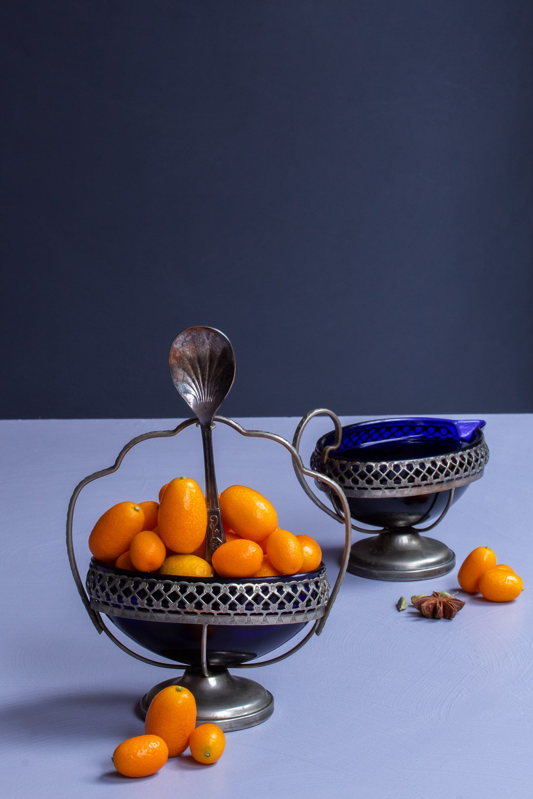 making cumquat brandy with blue glass bowl of cumquats and glass jug of brandy