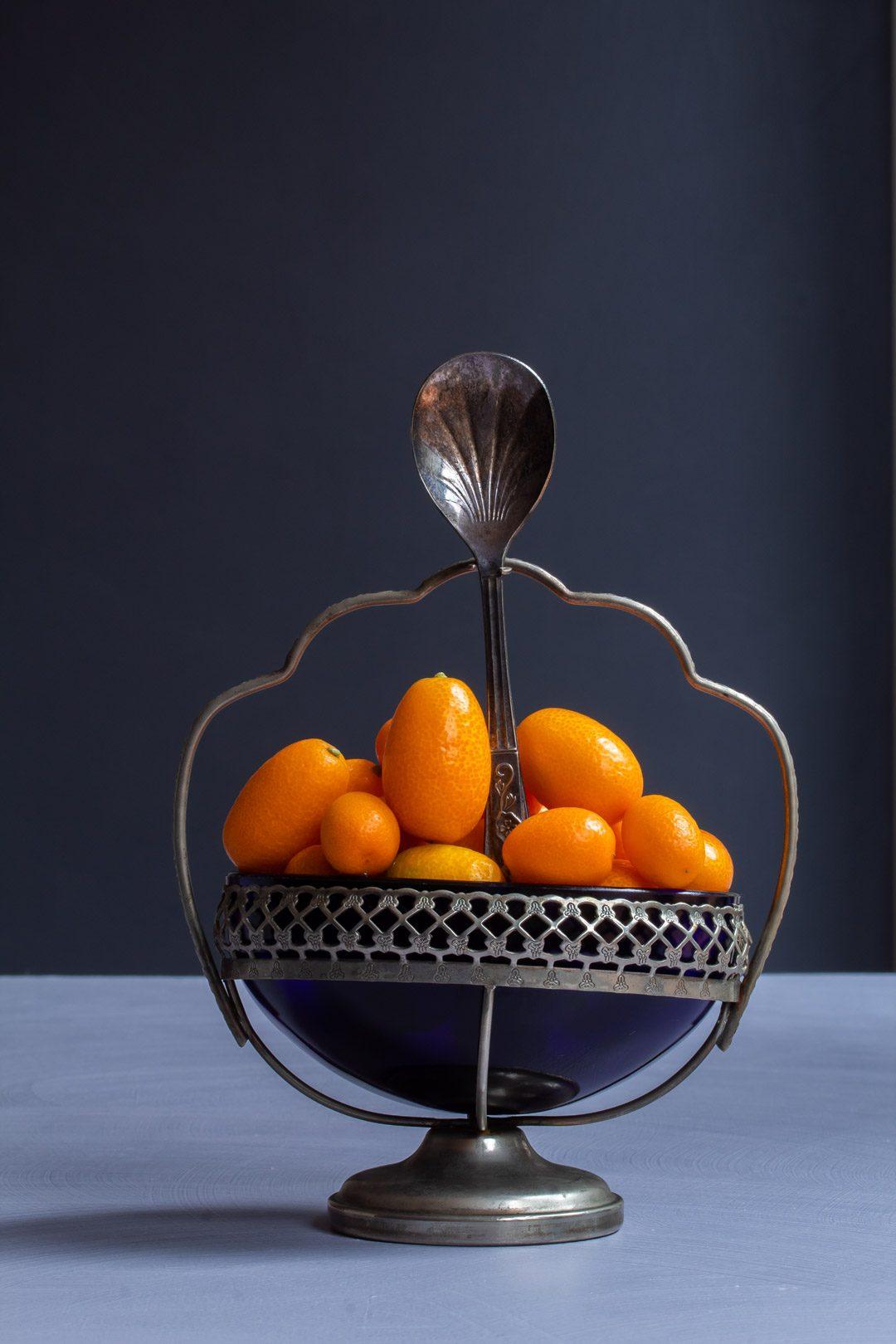 making cumquat brandy with cumquats in blue glass vintage sugar bowl with spoon