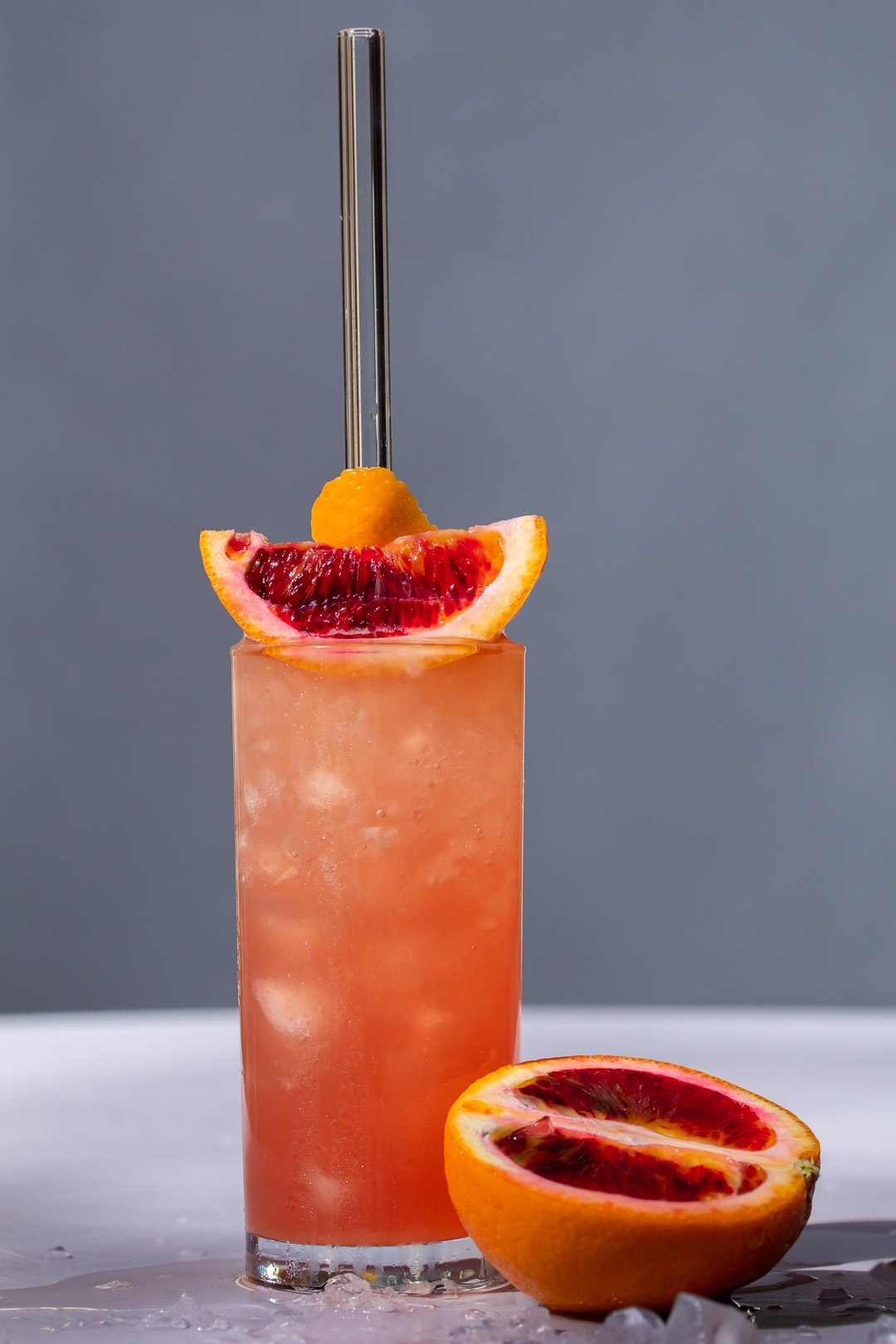 Improved blood orangeade on light purple and grey background with blood orange and ice