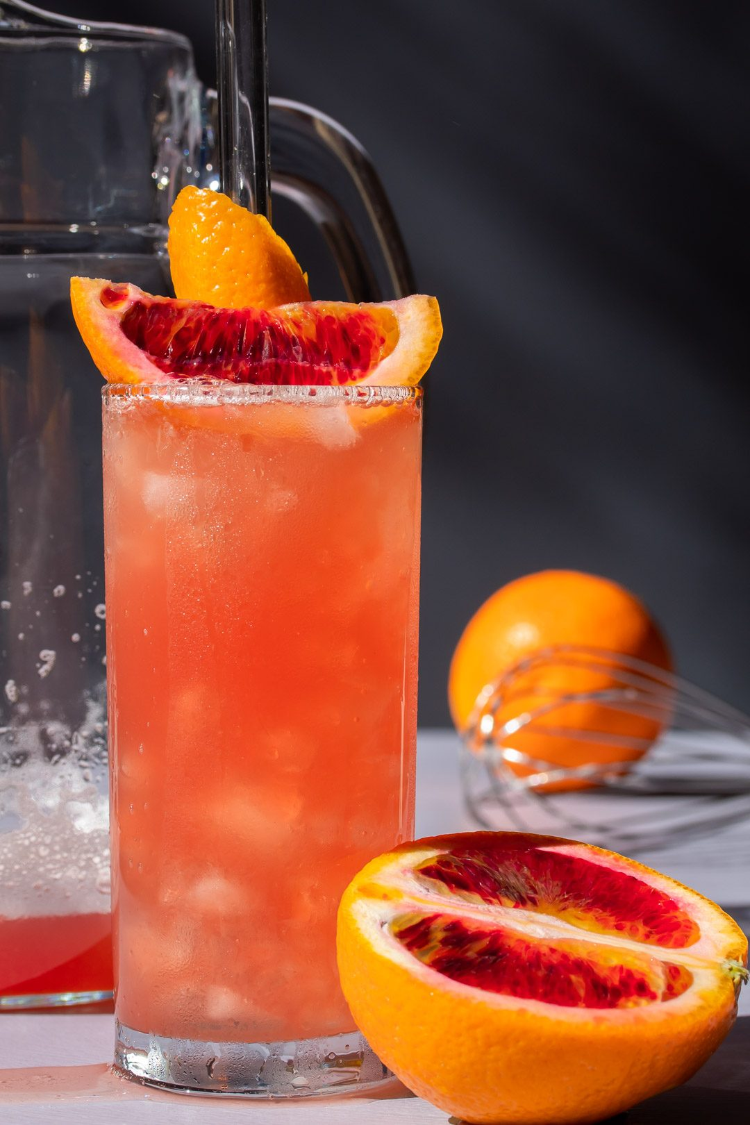 improved blood orangeade with jug, whisk and orange in background, cut blood orange in foreground