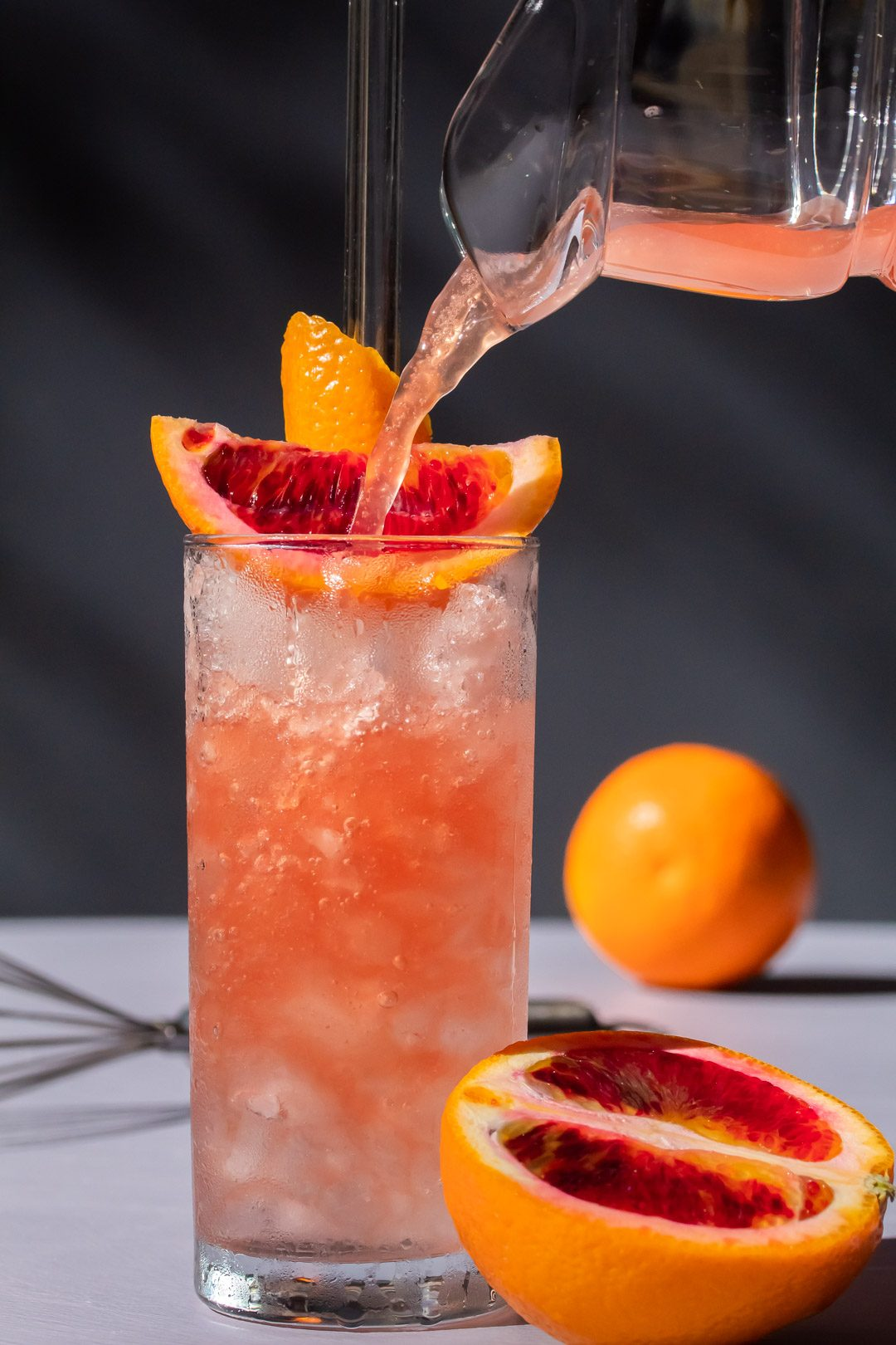 improved blood orangeade being poured into nearly full glass of crushed ice