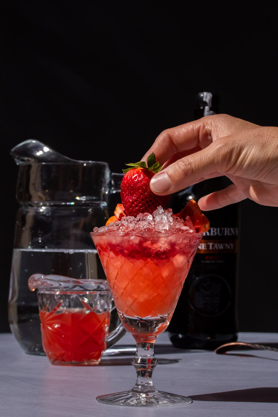 adding a fresh strawberry garnish to improved strawberry shrub