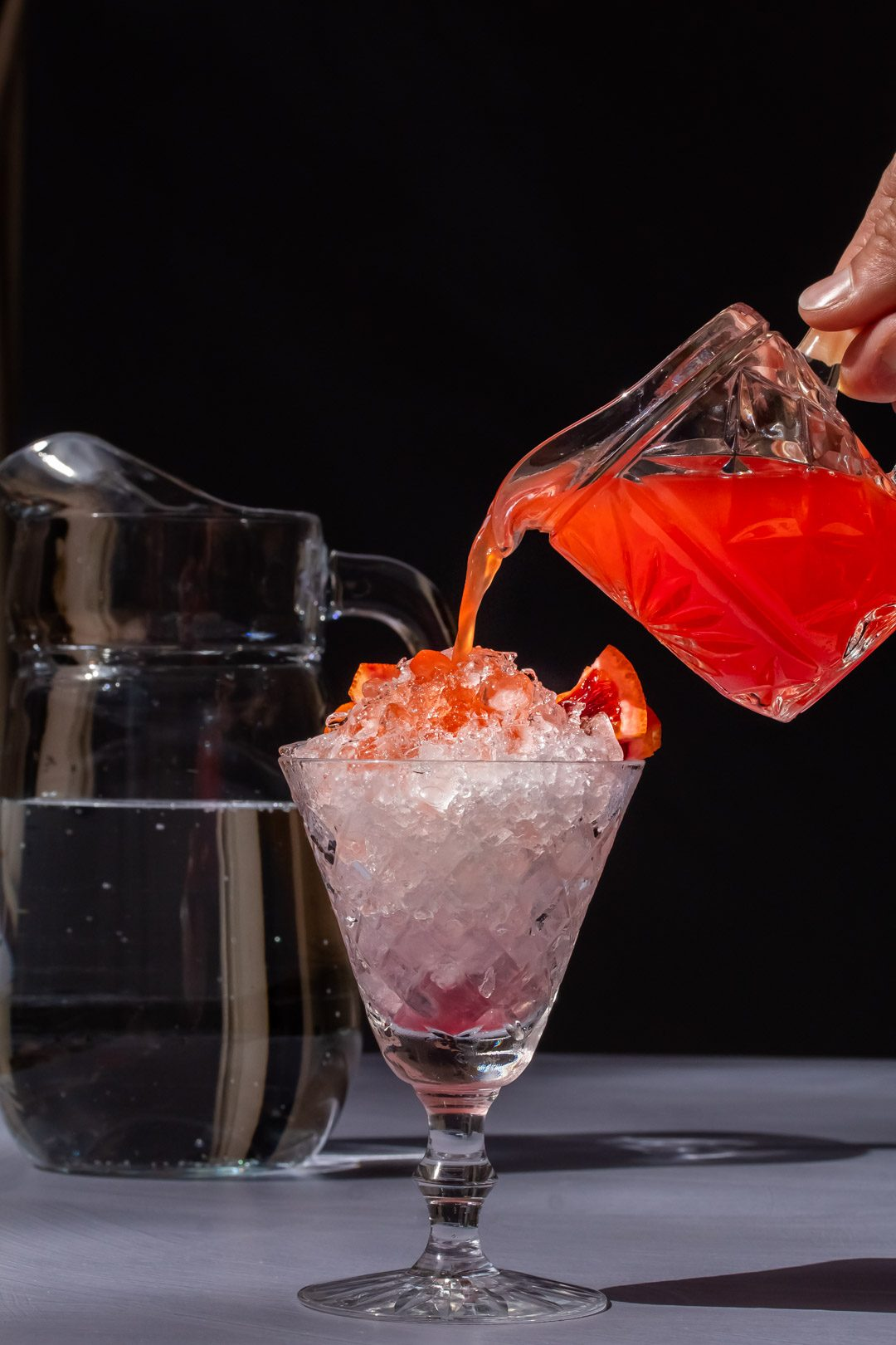 pouring improved strawberry shrub over crushed ice