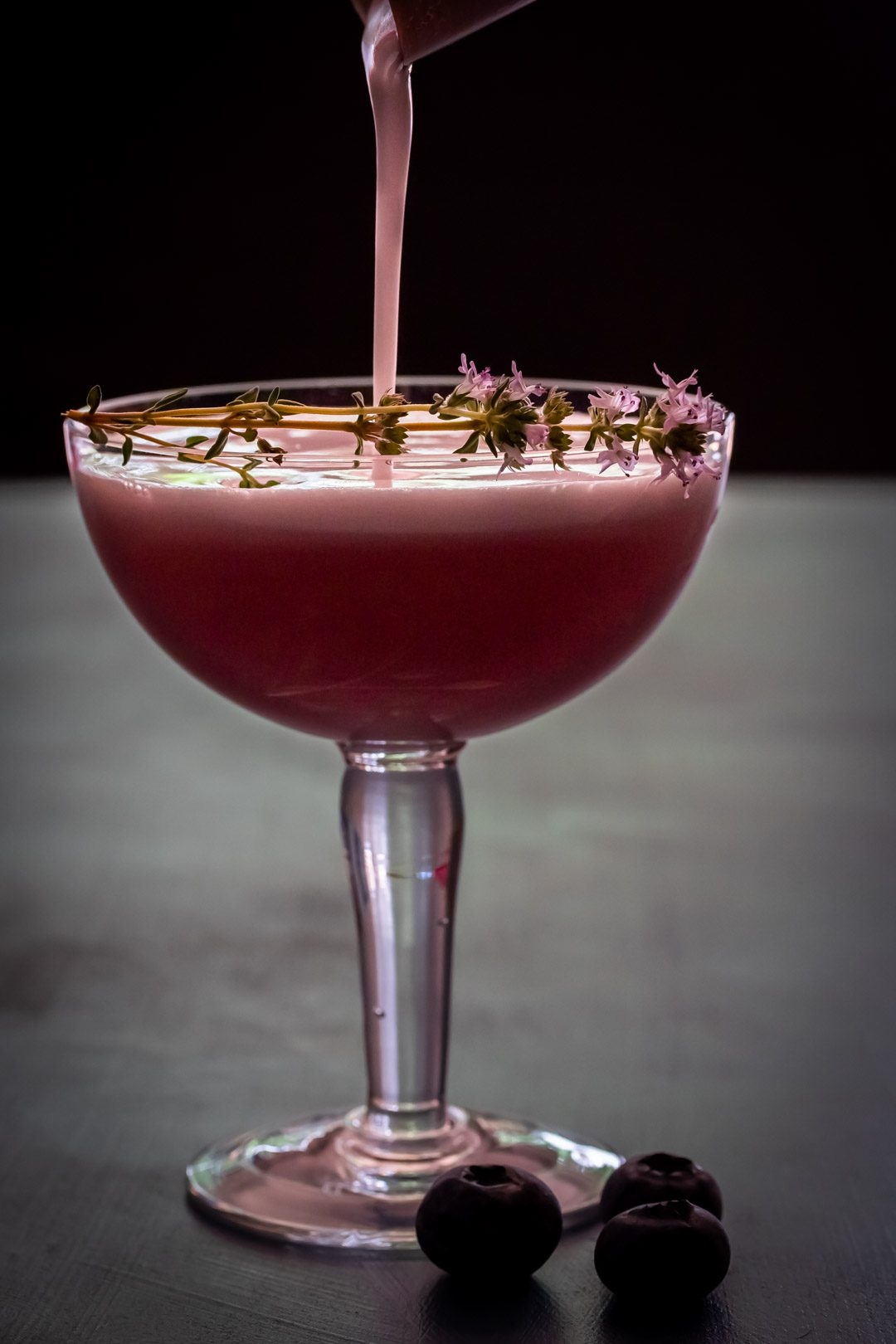 pouring a blueberry shrub pisco sour cocktail