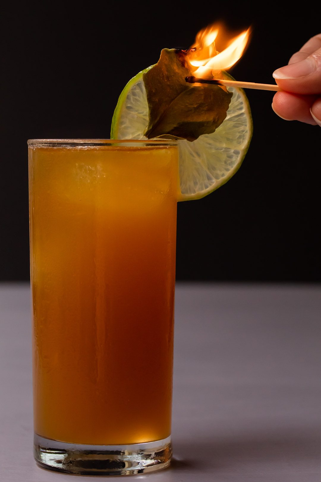 lime lightening dark 'n stormy with flamed kaffir lime leaf garnish