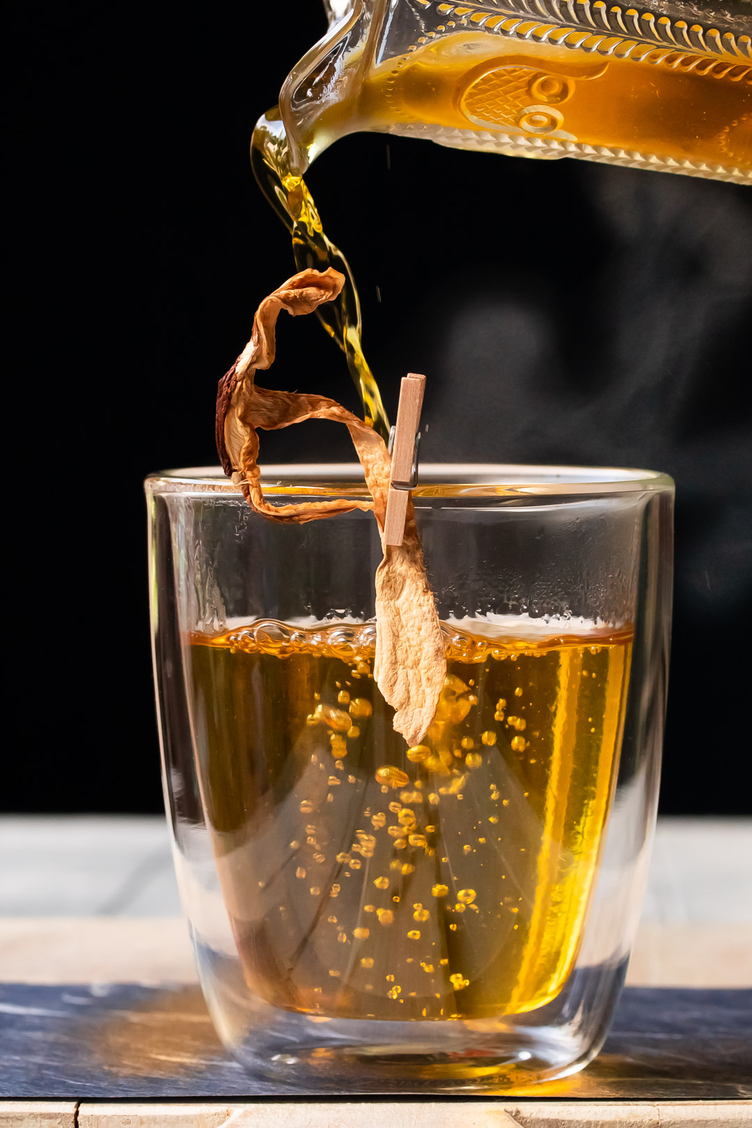 end pouring shiitake saffron infusion for umami hot whiskey toddy