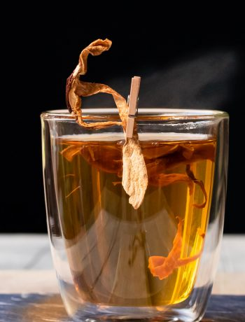 umami hot whiskey toddy with steam drifting to right