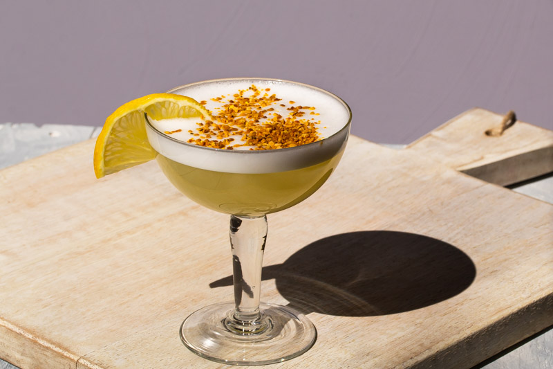 bee's knees silver sour with bee pollen and lemon garnish