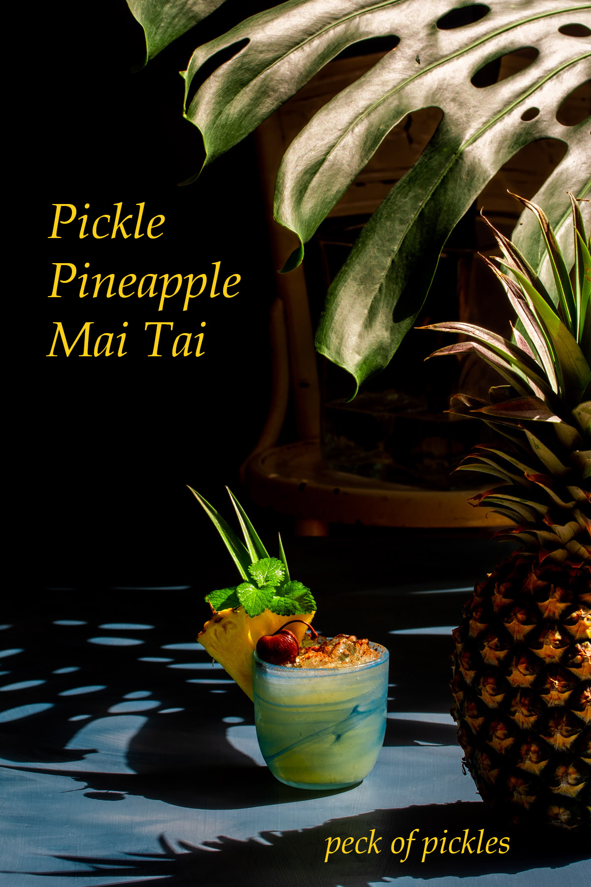 pickle pineapple shrub mai tai cocktail with pineapple in foreground and shadows in background