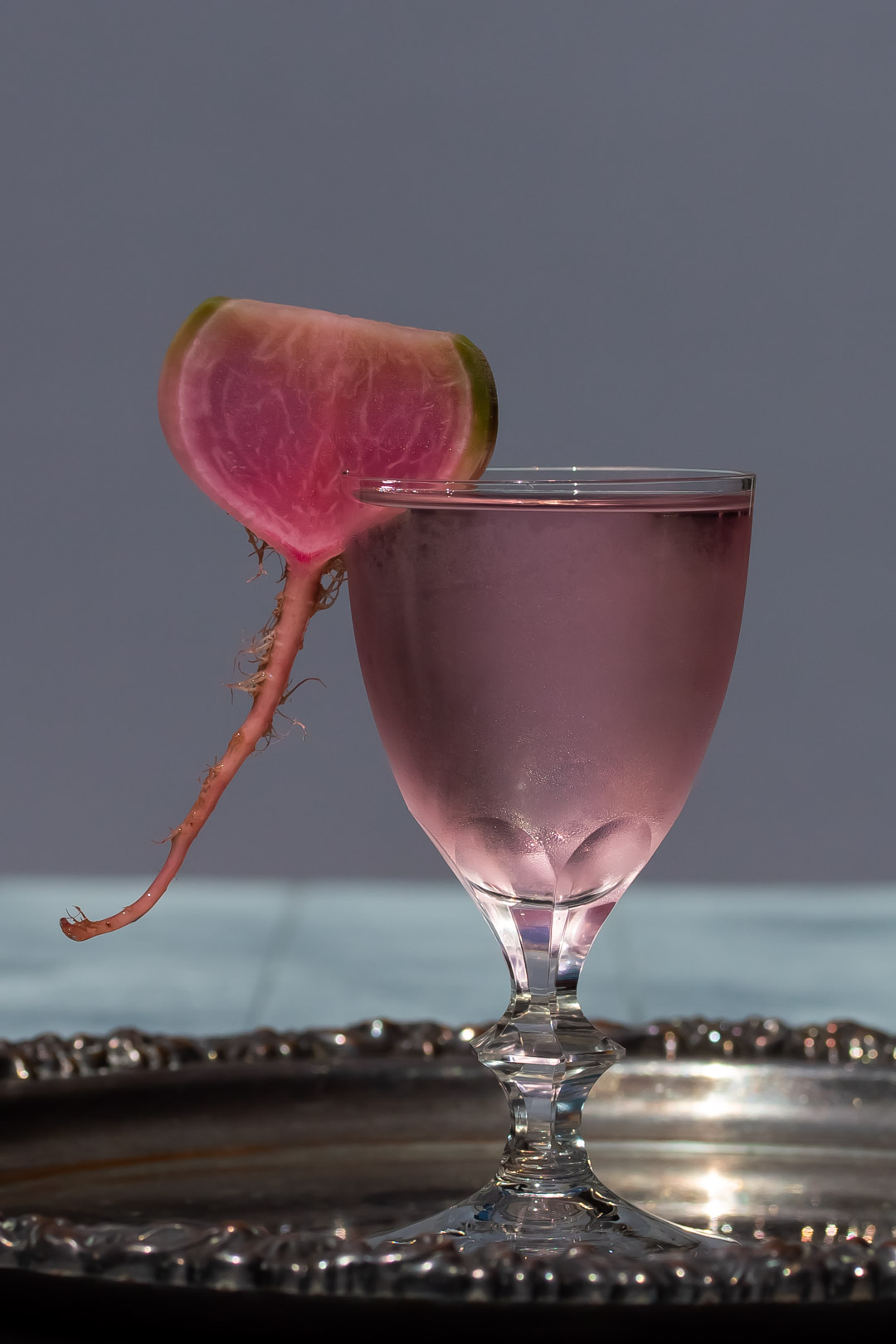 fermented watermelon radish martini on silver tray with blurred background