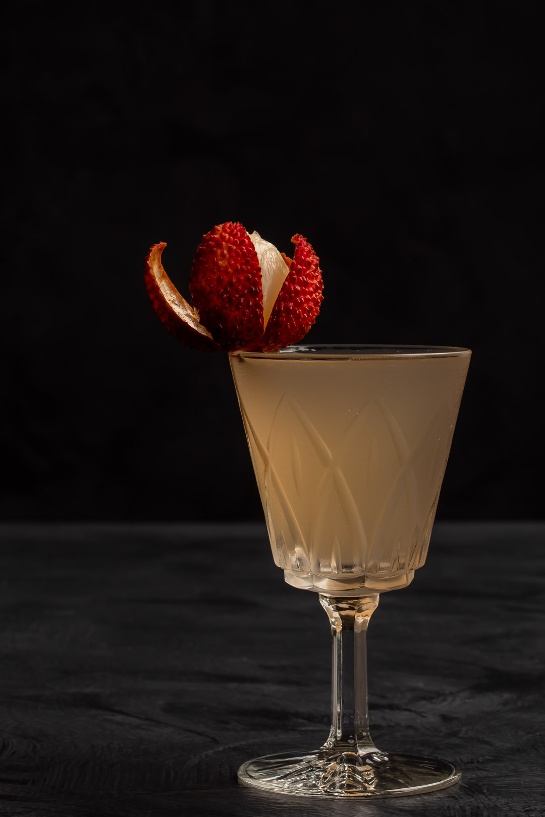 lychee reviver cocktail to right of frame with lychee garnish