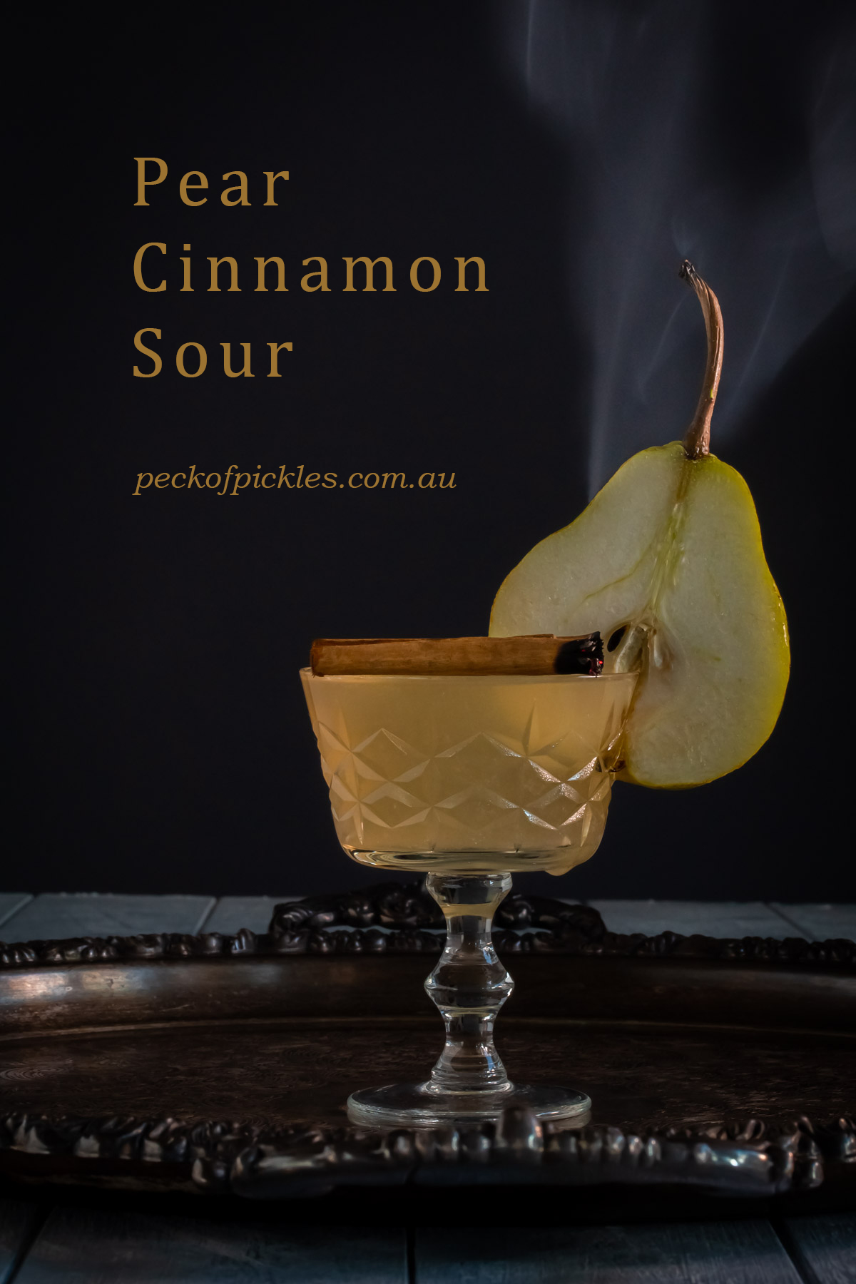 pear cinnamon sour on silver tray with pear slice and cinnamon smoke